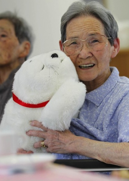 A Fukushima refugee cuddles PARO robot - designed to evoking caring responses in the elderly. Click picture to link for news story.