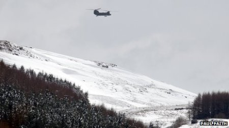 A helicopter delivering emergency supplies to farmers in Northern Ireland. Picture Credit Paul Faith/BBC