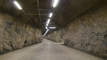 The tunnel descends, carved out of solid granite.