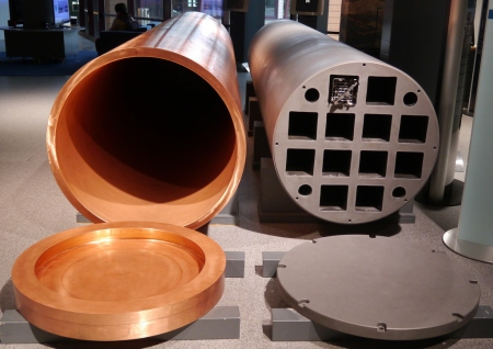 Fuel rod bundles (one visible) are placed in a cast Iron frame (right) chosen for its strength. This is then plced inside a copper cylinder chosen for its corrosion properties.
