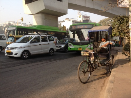 Street scene: bicycle rickshaw, tuk-tuk, cars, buses and the metro sweep over them all