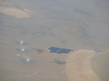 The three solar collectors of the Ivanpah solar plant together with a vast solar photo-voltaic array